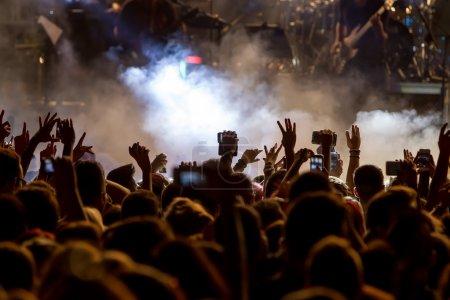 Photo pour Personnes qui prennent des photos avec le téléphone intelligent tactile lors d'un concert public de musique divertissement - image libre de droit