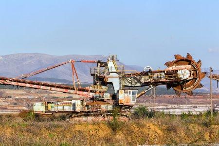 Photo pour Une excavatrice à roue à godets géante à l'oeuvre dans une mine de lignite avec un chemin de terre qui y mène au premier plan - image libre de droit