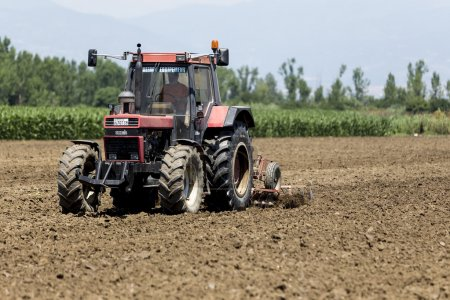 A tractor working planting wheat in the fertile farm fields of G