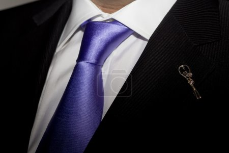 Man in black suit with purple tie and broach