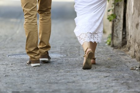 Young couple walking outdoor. Male and female legs.