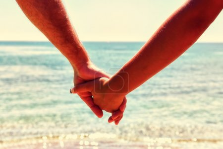Photo for Couple hands in a sky and sea close-up. Cross processed image for vintage look - Royalty Free Image