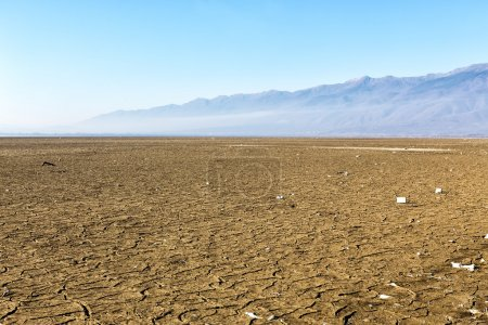 Dry lake bed with natural texture of cracked clay in perspective