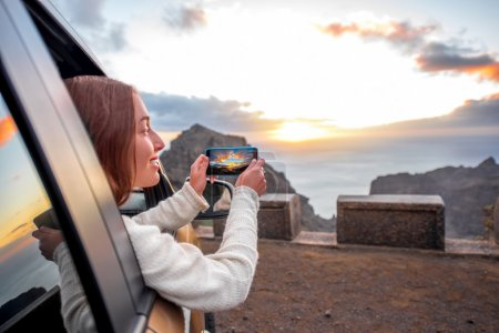 Photo for Young female traveler photographing with smartphone beautiful rocky coast on the sunset. Woman enjoying sunset sitting and looking out the car window - Royalty Free Image
