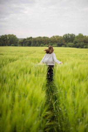 Mujer relajada de pie en el campo verde y disfruta de la naturaleza tranquila