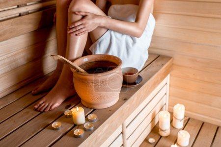 Photo pour Jeune femme dans une serviette blanche se reposer au sauna finlandais - image libre de droit