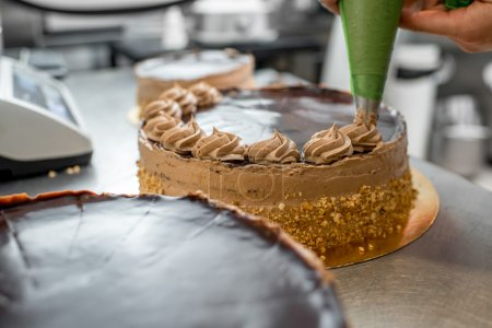 Photo for Woman making biscuit cake with nuts and chocolate at the bakery - Royalty Free Image