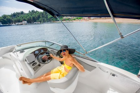 Photo pour Young and pretty woman in yellow skirt and swimsuit with hat and sunglasses driving luxury yacht in the sea. Top view with copy space - image libre de droit