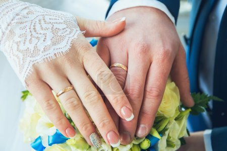 Photo for Hands with wedding rings on a bouquet of flowers - Royalty Free Image