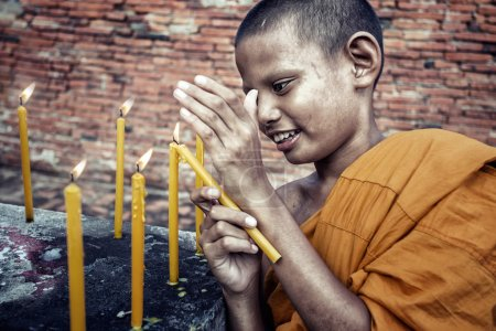 Photo for Young Novice are lighting candles worship at Ayutthaya historical park in Thailand - Royalty Free Image