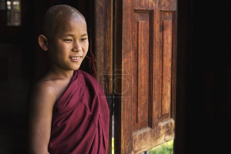 Photo for Happy novice Buddhist monk looking out the window at Indein village monastery in Inle Lake, Shan State, Myanmar (Burma). - Royalty Free Image