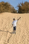 Afro boy walking in the sand, ten years old