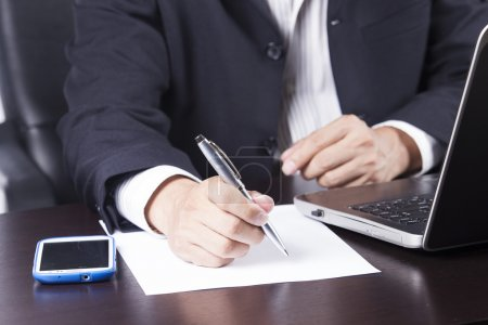 Business man's hands writing document