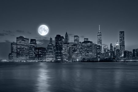 Photo for Panoramic view New York City Manhattan downtown skyline at night with skyscrapers blue tonality and bright full moon - Royalty Free Image
