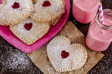 Photo for Heart shaped cherry hand pies dusted with powdered sugar sitting on pink plate with two glasses of strawberry milk with pink swirl straws - Royalty Free Image