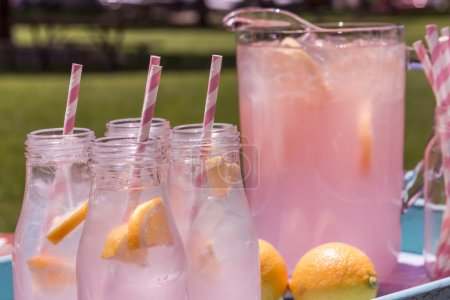 Photo for Close up of 4 small glass bottles and pitcher filled with fresh squeezed pink lemonade with pink swirled straws and lemon slices sitting on weather blue drink tray - Royalty Free Image