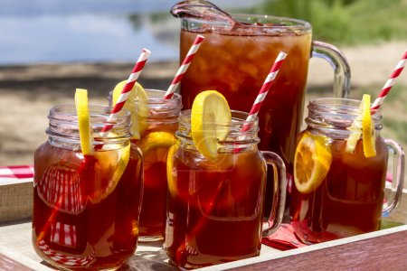 Photo for Pitcher and mason jar mugs filled with iced tea and lemons sitting on picnic table with Mount Garfield in Grand Junction, CO in the distance - Royalty Free Image