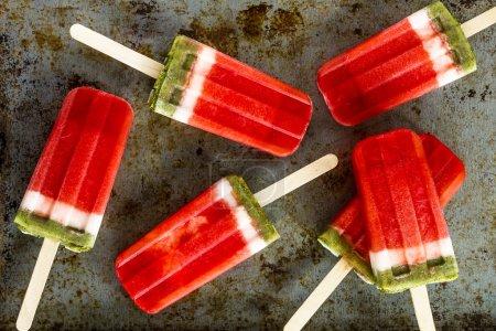 Photo pour Gelée de fruits melon et kiwi popsicles assis sur métal, plaque de cuisson - image libre de droit