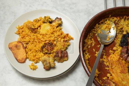 Teller mit im Ofen gebackenem Reis neben einer Steingutpfanne. Valencia, Spanien