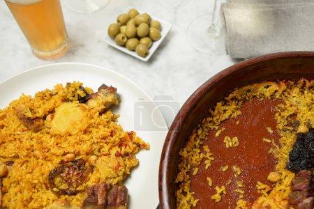 Paella-Teller, Oliven und ein Glas Bier auf einem Marmortisch. Valencia, Spanien