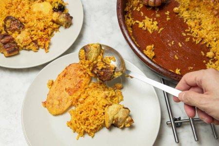 Menschenhände servieren im Ofen gebackenen Reis auf einem Teller mit einem Löffel. Valencia, Spanien
