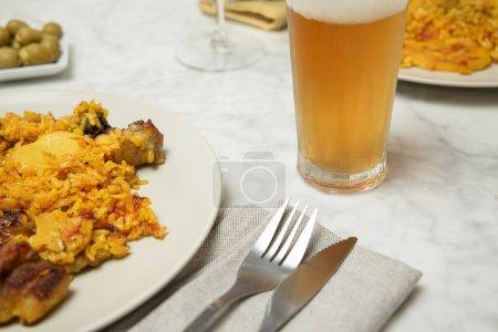 Zwei Paella-Teller mit Getränken und Besteck auf einem Marmortisch. Valencia, Spanien