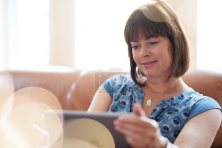 Photo for Serene lady in her forties reading emails on a wireless tablet in a brightly lit house- filtered image - Royalty Free Image