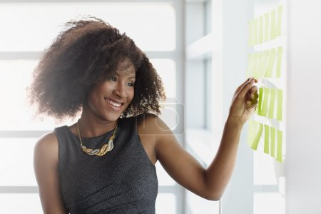 Photo for Friendly african american executive business woman brainstorming using green adhesive notes in a modern white office - Royalty Free Image