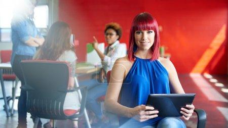 Photo pour Casual portrait d'une femme d'affaires rousse utilisant la technologie dans une startup clair et ensoleillée avec l'équipe en arrière-plan - image libre de droit