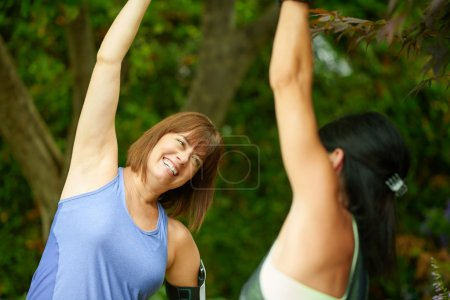 Two mature women keeping fit and streching before jogging