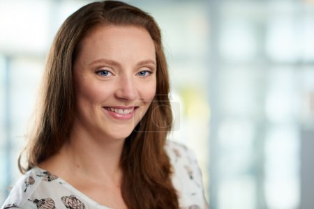 Horizontal headshot of an attractive caucasian business woman shot with shallow depth field.