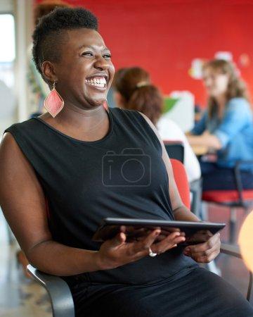 Photo pour Casual portrait d'une femme d'affaires afro-américains utilisant la technologie dans une startup clair et ensoleillée avec l'équipe en arrière-plan - image libre de droit