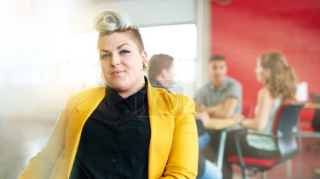 Photo for Casual portrait of a business woman using technology in a bright and sunny startup with the team in the background - Royalty Free Image