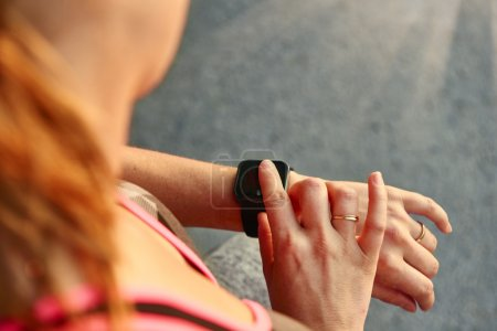 Woman programming her smartwatch before going jogging to track performance