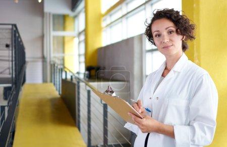 Foto de Amistoso y atractivo de una practicante hispana de pie en una oficina de vidrio de la clínica y examinando documentos - Imagen libre de derechos