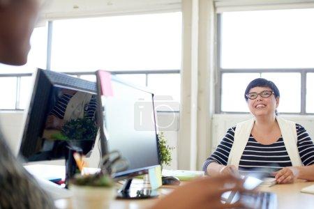 Photo pour Candid photo d'une femme patron et affaires équipe collaborant. Serie filtrée avec des fusées légères, bokeh, tons ensoleillés chauds. - image libre de droit