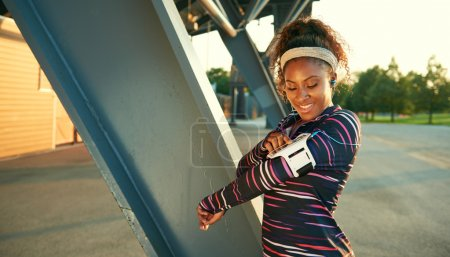 African american fit woman choosing music from an app for running at sunset