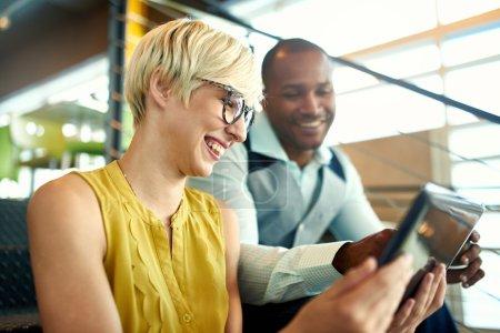zwei kreative Kleinunternehmer aus dem Millennium, die im Treppenhaus mit einem digitalen Tablet an einer Social-Media-Strategie arbeiten