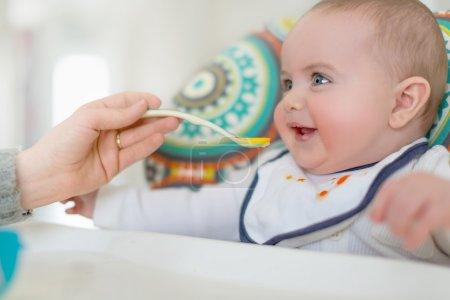 Photo pour Mère d'un adorable bambin d'alimentation alimentation bébé en bonne santé - image libre de droit