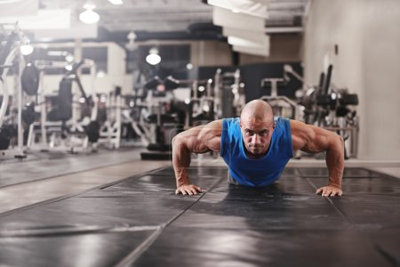 Photo for Active and muscular man keeping fit by doing pushups on a floor mat - filtered image - Royalty Free Image