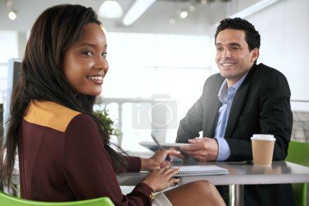 Photo pour Couple de collaborateurs d'entreprise collaborant sur un projet dans un bureau en verre lumineux - image libre de droit