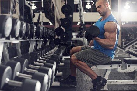 Photo pour Homme actif et musclé, gardant ses bras forts musculaire et en forme à l'aide de poids libres - filtré image - image libre de droit