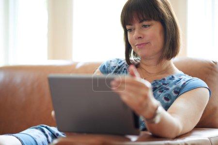 Photo pour Dame sereine dans la quarantaine lisant des courriels sur une tablette sans fil dans une image filtrée à la maison très éclairée - image libre de droit