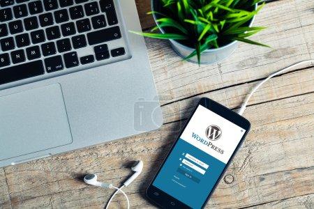 Wordpress-App auf einem Handy-Bildschirm. Blick von oben auf den hölzernen Arbeitsplatz.