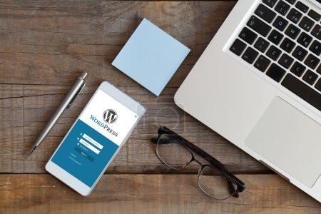 Wordpress-App auf einem Handy-Bildschirm. Draufsicht auf den Holztisch mit Computer, Brille, Stift und Post.