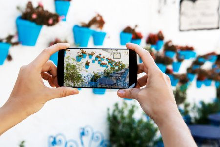 Female hands taking a picture with mobile phone in a white village in Andalusia.