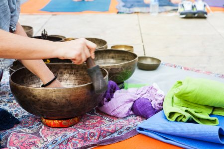 Hand playing yoga bowls outdoors.