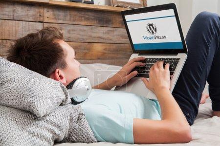 malaga, spanien - 10. November 2015: WordPress-Markenlogo auf dem Computerbildschirm. Mann tippt auf der Tastatur. Wordpress ist ein kostenloses Open-Source-Blogging-Tool und ein Content-Management-System (cms).