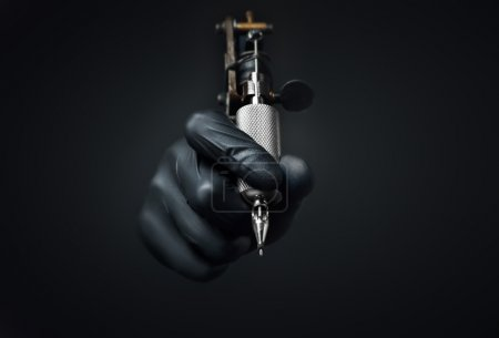 Photo for Tattoo artist holding tattoo machine on dark background, Machine for a tattoo concept - Royalty Free Image