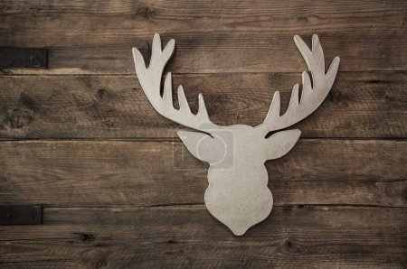Deer head with antler for christmas decoration on wooden backgro